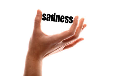 pain scale: Color horizontal shot of a of a hand holding the word sadness. Stock Photo