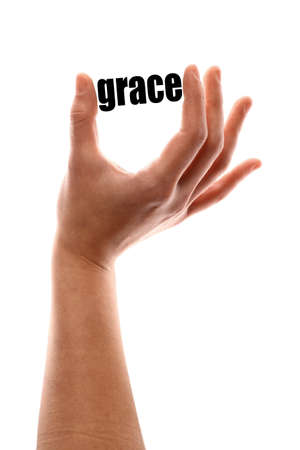 redemption: Color vertical shot of a of a hand holding the word grace.