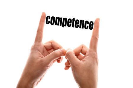 Color horizontal shot of two hands squeezing the word competence. Stock fotó
