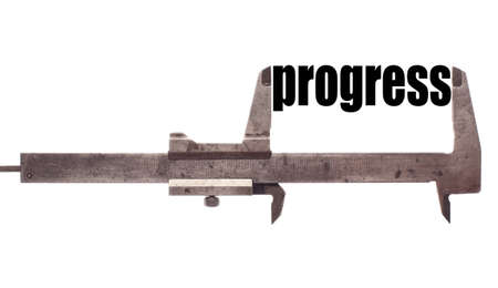 Color horizontal shot of a caliper and measuring the word progress.