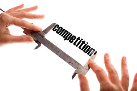 """competitividad: Color de tiro horizontal de dos manos sosteniendo una pinza y la medición de la palabra """"competencia"""". Foto de archivo"""