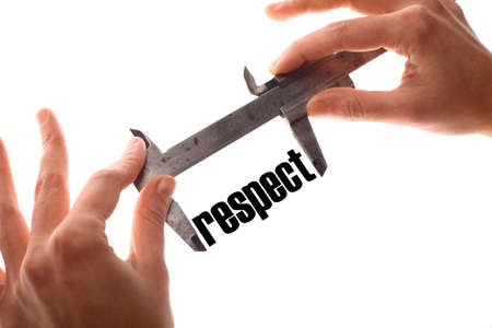 decency: Color horizontal shot of two hands holding a caliper and measuring the word respect. Stock Photo
