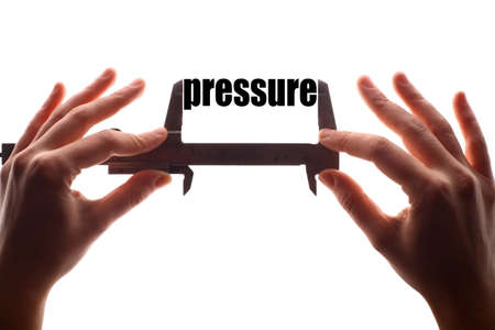 atmospheric pressure: Color horizontal shot of two hands holding a caliper and measuring the word pressure.