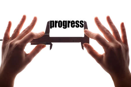 Color horizontal shot of two hands holding a caliper and measuring the word progress.