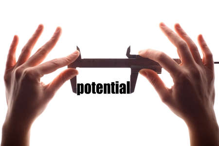 potential: Color horizontal shot of two hands holding a caliper and measuring the word potential. Stock Photo