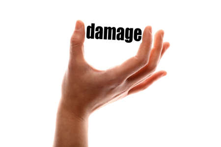 compensate: Color horizontal shot of a of a hand squeezing the word damage. Stock Photo
