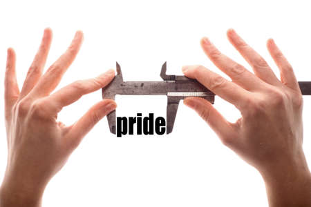 homosexuality: Color horizontal shot of two hands holding a caliper and measuring the word pride.