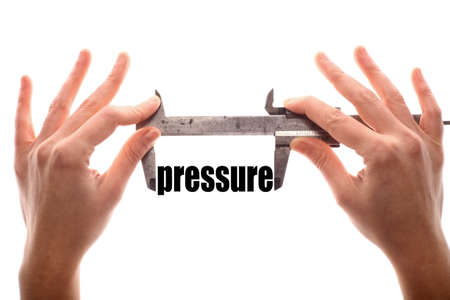 atmospheric: Color horizontal shot of two hands holding a caliper and measuring the word pressure.