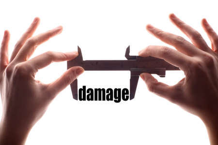 compensate: Color horizontal shot of two hands holding a caliper and measuring the word damage.