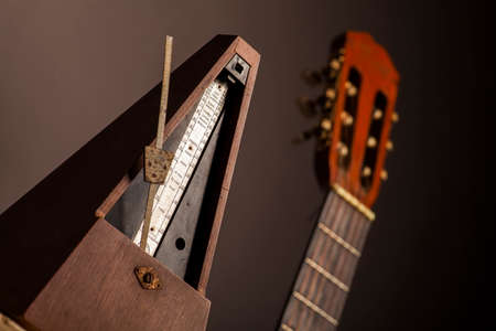 allegro: Color shot of a vintage metronome, next to an acoustic guitar, on a black .