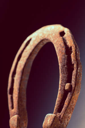 horse shoe: Color shot of a rusty horse shoe on a dark . Stock Photo