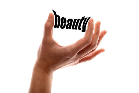 exact: Color horizontal shot of a of a hand squeezing the word beauty.