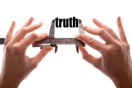untrue: Color horizontal shot of two hands holding a caliper and measuring the word truth. Stock Photo