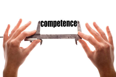 Color horizontal shot of two hands holding a caliper and measuring the word competence. Stock Photo