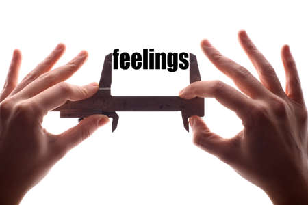feelings: Color horizontal shot of two hands holding a caliper and measuring the word feelings.