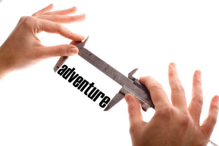 wanderlust: Color horizontal shot of two hands holding a caliper and measuring the word adventure. Stock Photo
