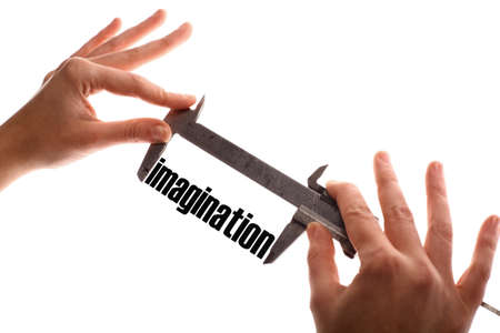 exact: Color horizontal shot of two hands holding a caliper and measuring the word imagination.