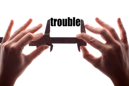 in trouble: Color horizontal shot of two hands holding a caliper and measuring the word trouble. Stock Photo