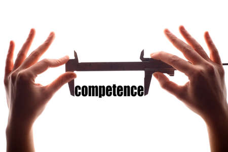 competence: Color horizontal shot of two hands holding a caliper and measuring the word competence. Stock Photo