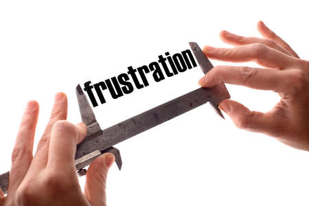 unachievable: Color horizontal shot of two hands holding a caliper and measuring the word frustration. Stock Photo