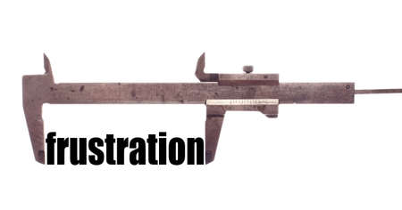 unachievable: Color horizontal shot of a caliper and measuring the word frustration.