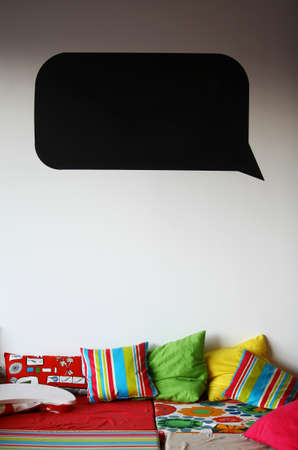 dialog baloon: A black speech bubble on a wall above a bed. Stock Photo
