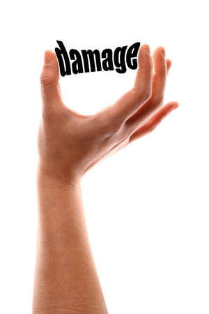 compensate: Color vertical shot of a of a hand squeezing the word damage. Stock Photo