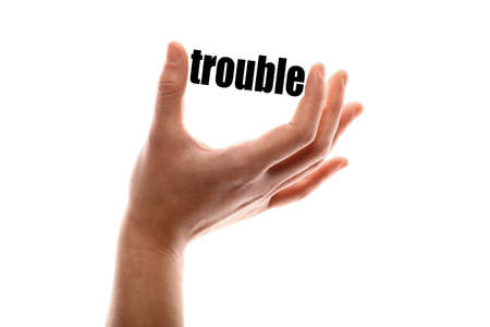 in trouble: Color horizontal shot of a of a hand squeezing the word trouble. Stock Photo