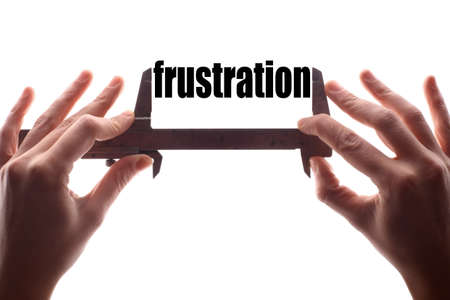 overcoming adversity: Color horizontal shot of two hands holding a caliper and measuring the word frustration. Stock Photo
