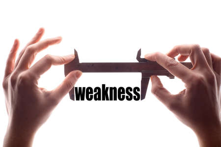 weakness: Color horizontal shot of two hands holding a caliper and measuring the word weakness.