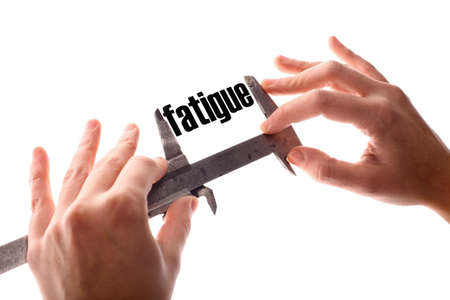 fatigue: Color horizontal shot of two hands holding a caliper and measuring the word fatigue. Stock Photo