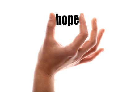 exact: Color horizontal shot of a hand squeezing the word hope.