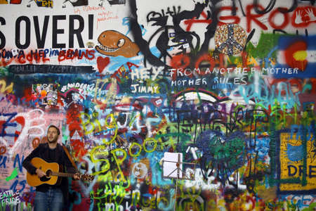 john lennon: Prague, Czech Republic - June 9, 2015: Color image of a street performer playing the guitar in front of the John Lennon wall in Prague, Czech Republic. Editorial