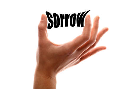 misery: Color horizontal shot of a hand squeezing the word sorrow. Stock Photo