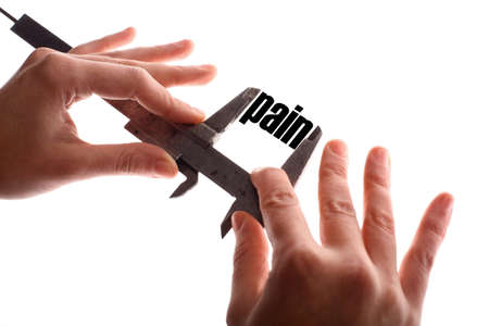 pain scale: Color horizontal shot of two hands holding a caliper and measuring the word pain. Stock Photo
