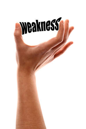 weakness: Color vertical shot of a of a hand squeezing the word weakness.