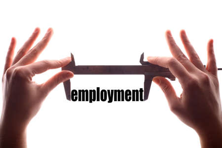 jobless: Color horizontal shot of two hands holding a caliper and measuring the word employment. Stock Photo