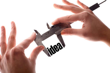 invent clever: Color horizontal shot of two hands holding a caliper and measuring the word idea.