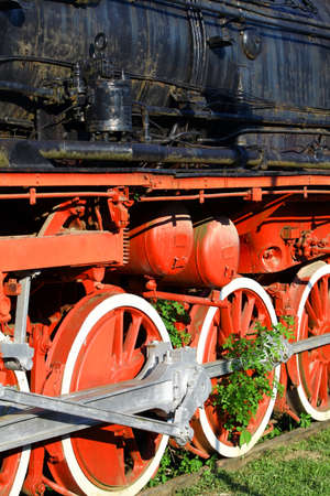 steam locomotives: Color image of an abandoned steam locomotives wheels, with plants growing around them. Stock Photo