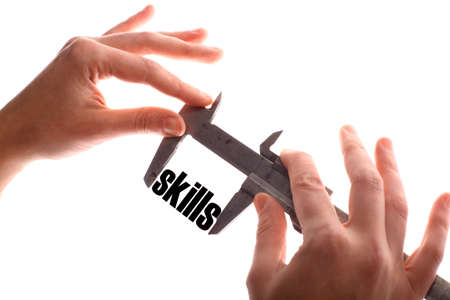 leading education: Color horizontal shot of two hands holding a caliper and measuring the word skills.