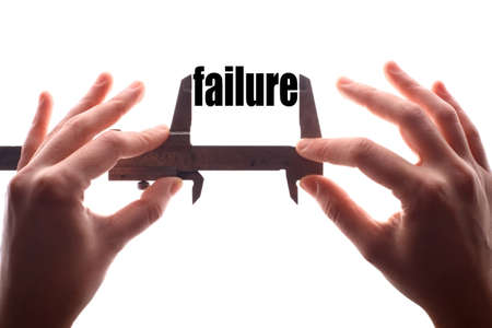 caliper: Color horizontal shot of two hands holding a caliper and measuring the word failure. Stock Photo