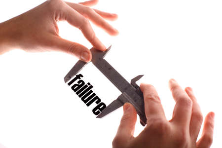 exact: Color horizontal shot of two hands holding a caliper and measuring the word failure. Stock Photo