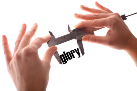 exact: Color horizontal shot of two hands holding a caliper and measuring the word glory.
