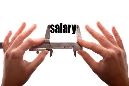 salaries: Color horizontal shot of two hands holding a caliper and measuring the word salary. Stock Photo