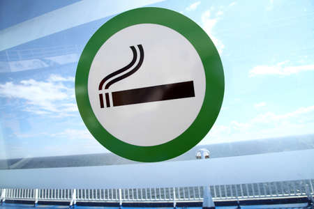 designated: Picture of a sign marking the designated smoking area on a window. Stock Photo