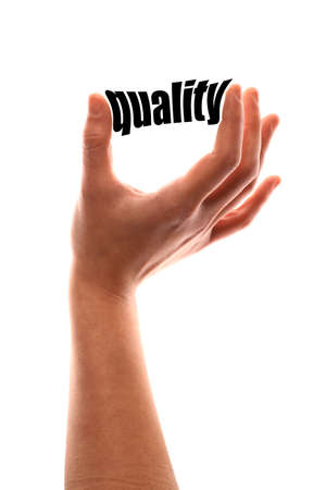 superiority: Color vertical shot of a of a hand squeezing the word quality.