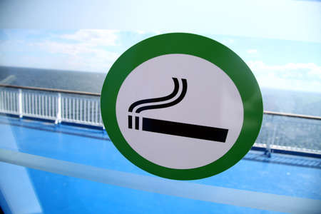 a public notice: Picture of a sign marking the designated smoking area on a window. Stock Photo