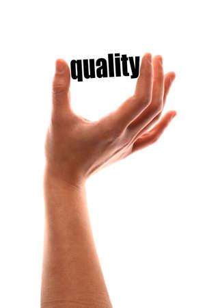 """ottimo: colpo verticale di colore di una di una mano spremitura la parola """"qualità""""."""