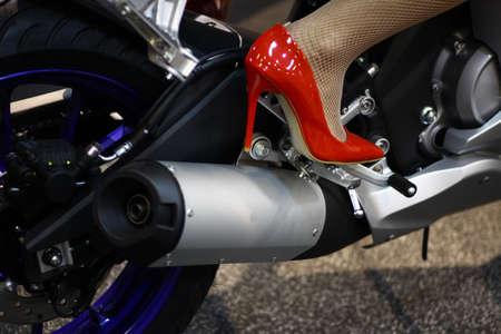 tacones rojos: imagen en color de los tubos de escape de una motocicleta y una pierna de una mujer, con tacones rojos. Foto de archivo
