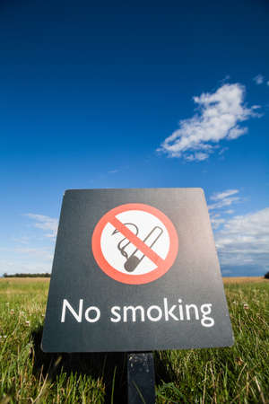 abstain: Color image of a No Smoking sign on a on a meadow.